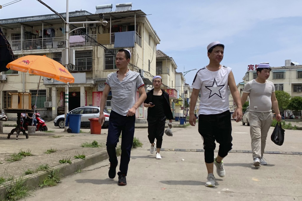 In this June 5, 2019, photo, residents of the Hui Muslim ethnic minority walk in a neighborhood near an OFILM factory in Nanchang in eastern China's J...