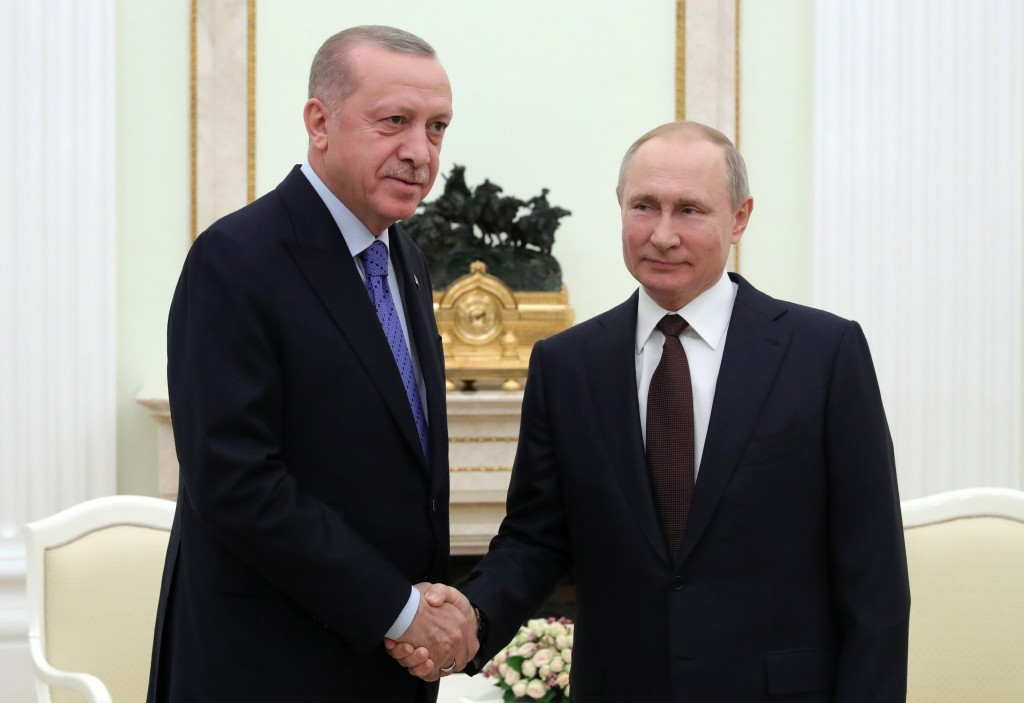 Russian President Vladimir Putin, right, and Turkish President Recep Tayyip Erdogan shake hands during their meeting in the Kremlin, in Moscow, Russia...