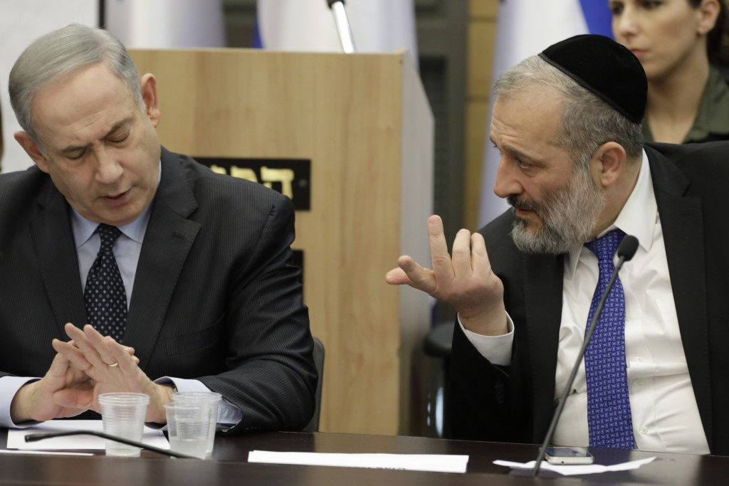 Israeli Prime Minister Benjamin Netanyahu listens to Israeli Interior Minister Aryeh Deri during a meeting with his nationalist allies and his Likud p...