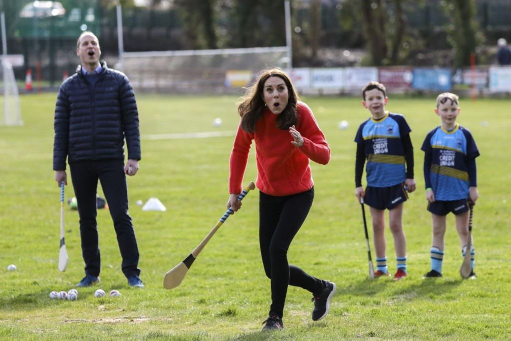 Kate the Duchess of Cambridge, center, gestures as she tries hurling next to Britain's Prince William at Salthill Knocknacarra GAA Club in Galway, Ire...