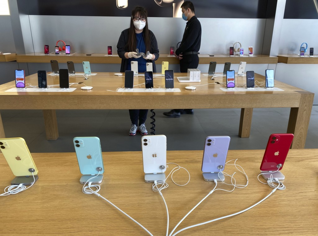 In this Feb. 26, 2020, photo, a worker polishes iPhones in an Apple store in Beijing. In a lively Muslim quarter of Nanchang city in eastern China, a ...