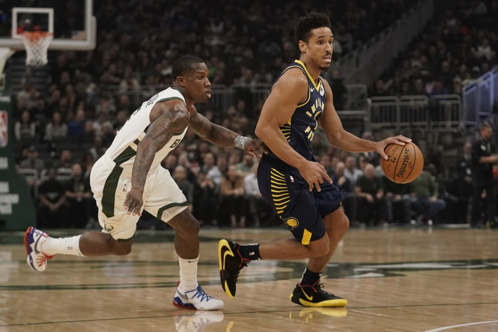 Indiana Pacers' Malcolm Brogdon drives past Milwaukee Bucks' Eric Bledsoe during the first half of an NBA basketball game Wednesday, March 4, 2020, in...