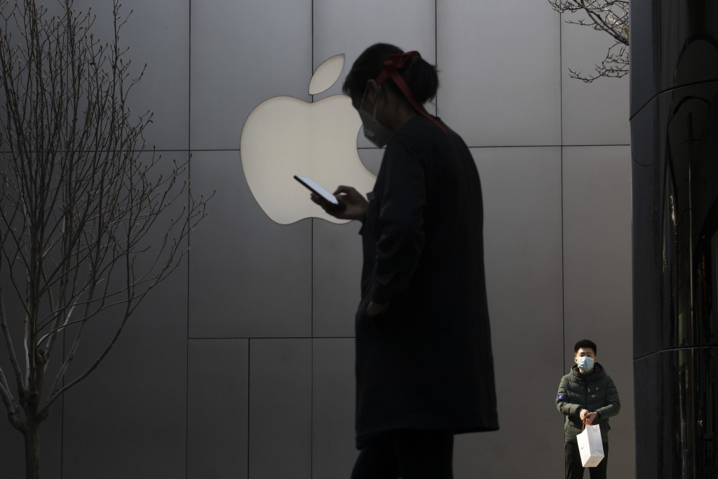 In this Feb. 26, 2020, photo, a woman uses her phone near the Apple store in Beijing. In a lively Muslim quarter of Nanchang city in eastern China, a ...
