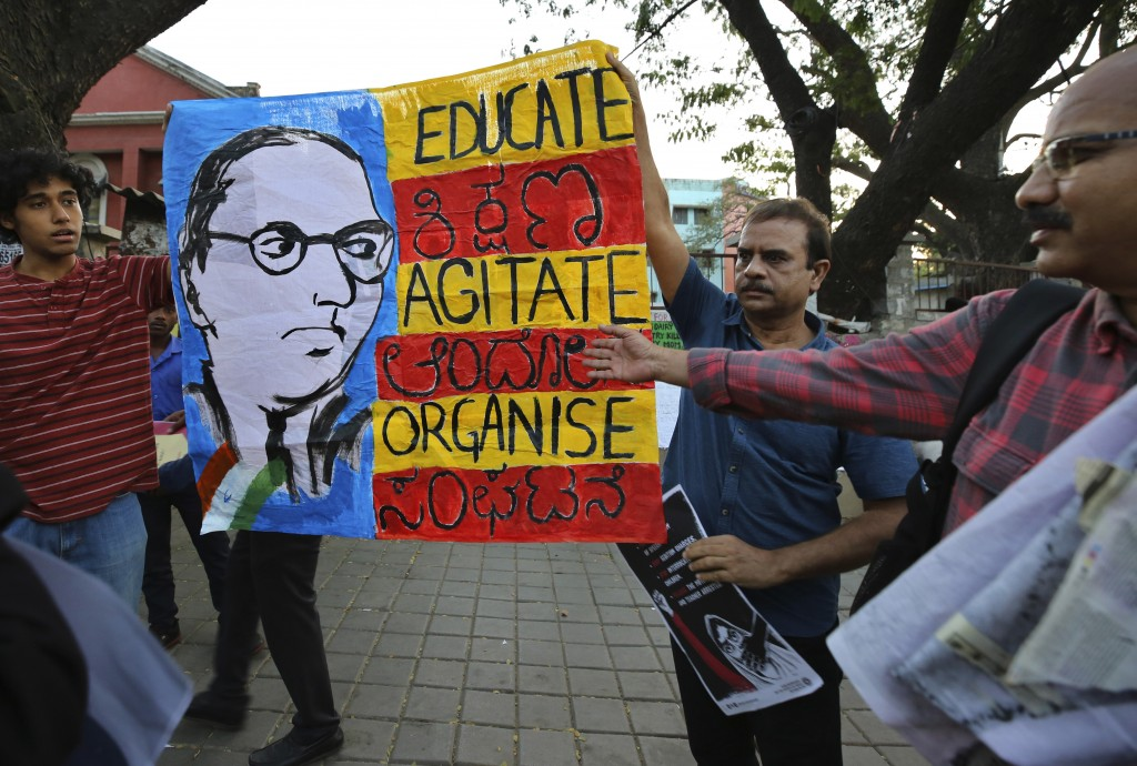 In this Tuesday, Feb. 4, 2020 photo, Indians hold a banner featuring sketch of Bhim Rao Ambedkar, the freedom fighter who is also regarded as the arch...