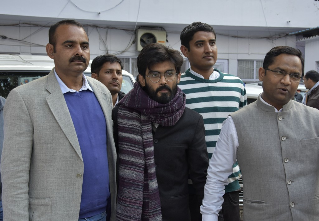 FILE - In this Wednesday, Jan. 29, 2020 file photo, plain clothes policemen escort Indian student Sharjeel Imam, center, as he is brought to be produc...