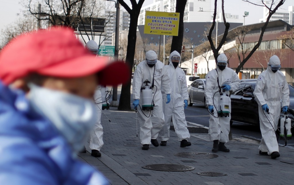 South Korean soldiers wearing protective gears spray disinfectant as a precaution against the new coronavirus on a street in Seoul, South Korea, Frida...