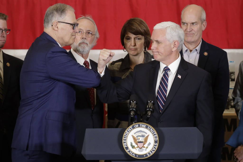 Vice President Mike Pence bumps elbows with Washington Gov. Jay Inslee, left, during a news conference, Thursday, March 5, 2020, at Camp Murray in Was...