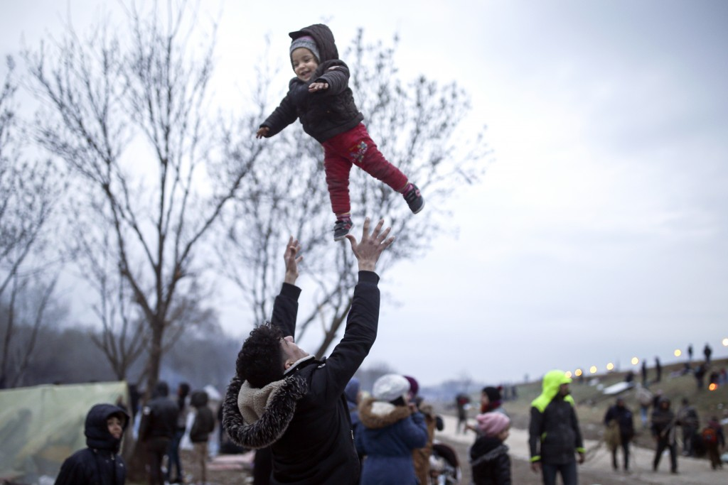 A migrant throws a baby in the air in Edirne near the Turkish-Greek border on Thursday, March 5, 2020. Turkey said Thursday it would deploy special fo...