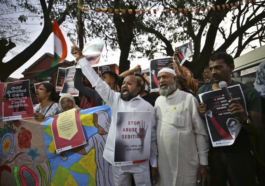 In this Tuesday, Feb. 4, 2020 photo, Indians hold placards and shout slogans during a protest against the sedition case filed by police against a scho...