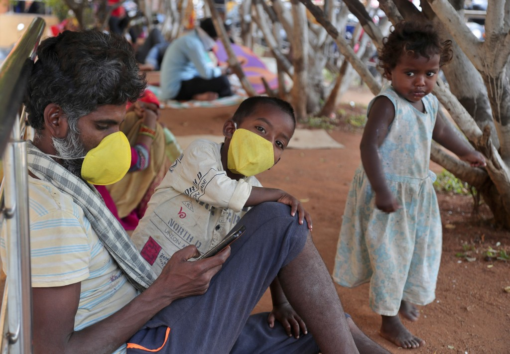 An Indian man and a child wearing masks wait outside the government run Gandhi Hospital in Hyderabad, India, Friday, March 6, 2020. For weeks India wa...