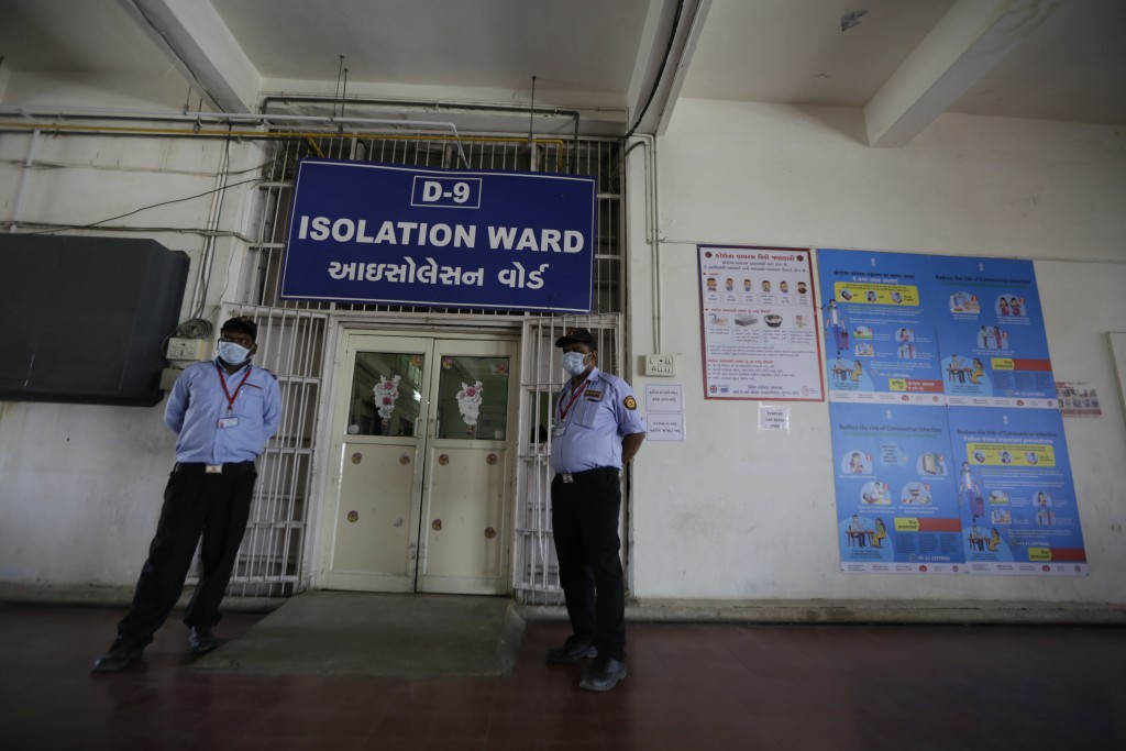 Indian security guards wearing masks stand outside a special ward set aside for possible COVID-19 patients at a government run hospital in Ahmedabad, ...