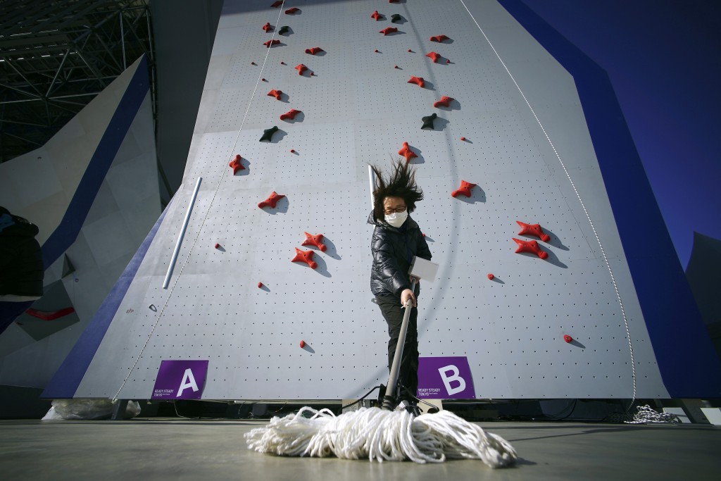 A Tokyo 2020 Olympic Games Organizing staff mops the floor in front of the climbing wall in the test event of Speed Climbing in preparation for the To...