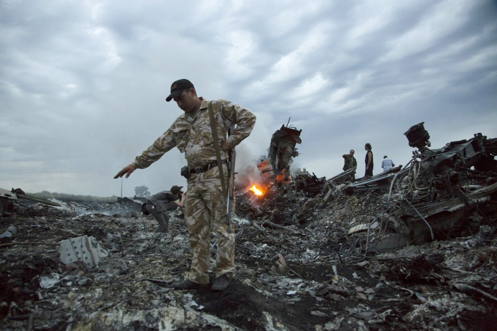 FILE- In this July 17, 2014, file photo, people walk amongst the debris at the crash site of MH17 passenger plane near the village of Grabovo, Ukraine...