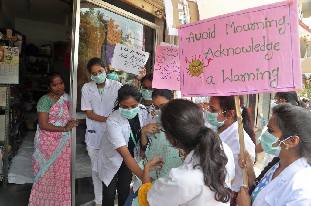 Indian students explain to a woman how to prevent COVID-19 during an awareness rally in Hyderabad, India, Friday, March 6, 2020. For weeks India watch...