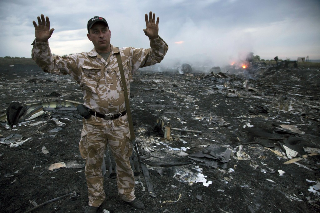 FILE- In this Thursday, July 17, 2014 file photo, a man gestures at a crash site of a passenger plane near the village of Grabovo, Ukraine. United by ...