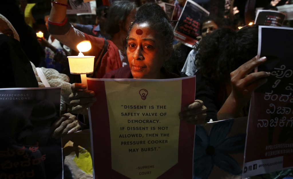 In this Tuesday, Feb. 4, 2020 photo, an Indian woman holds a candle and placard during a protest against the sedition case filed by police against a s...