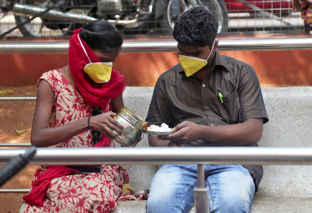 An Indian couple wearing masks prepare to eat their lunch at government run Gandhi Hospital in Hyderabad, India, Friday, March 6, 2020. For weeks Indi...