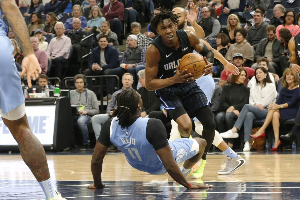 Orlando Magic's Wes Iwundu, center top, bowls over Minnesota Timberwolves' Naz Reid as he drives in the first half of an NBA basketball game, Friday, ...