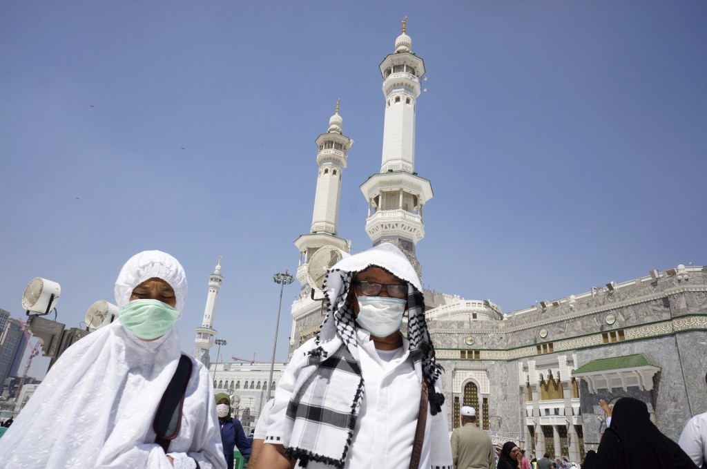 Muslim worshippers wear masks after the noon prayers outside the Grand Mosque, in the Muslim holy city of Mecca, Saudi Arabia, Saturday, March 7, 2020...