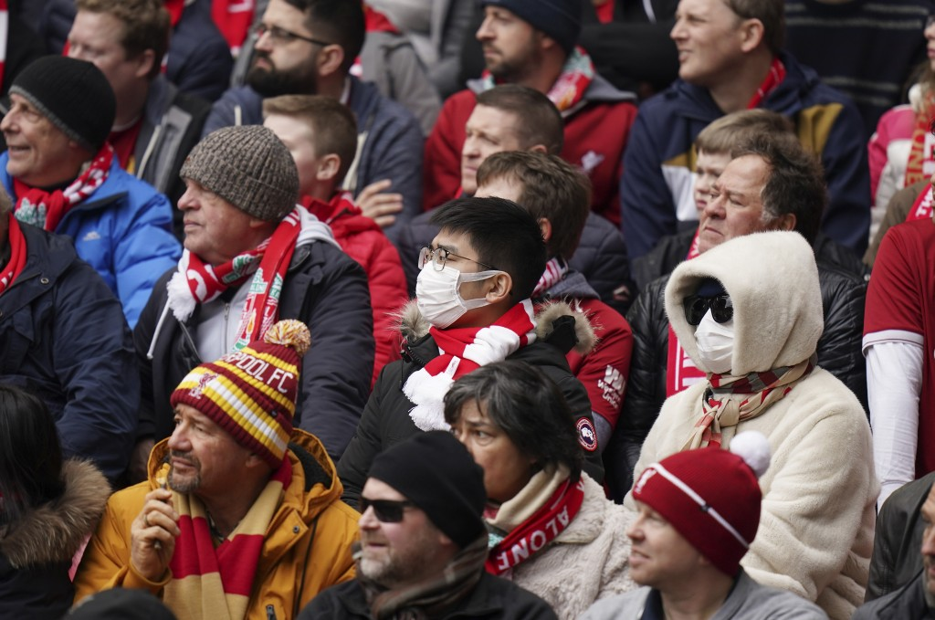 A fan wearing a protective mask attends at the English Premier League soccer match between Liverpool and Bournemouth at Anfield stadium in Liverpool, ...