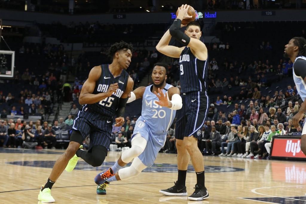 Minnesota Timberwolves' Josh Okogie, center, makes his way between Orlando Magic's Wes Iwundu, left, and Nikola Vucevic in the first half of an NBA ba...