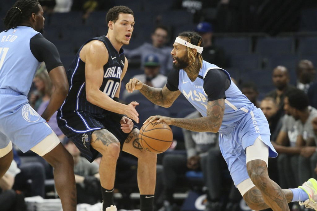 Minnesota Timberwolves' James Johnson, right, drives past Orlando Magic's Aaron Gordon in the first half of an NBA basketball game, Friday, March 6, 2...