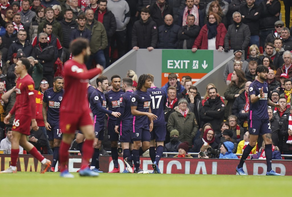 Bournemouth's Callum Wilson, covered by his teammates, celebrates after scoring his side's opening goal during the English Premier League soccer match...