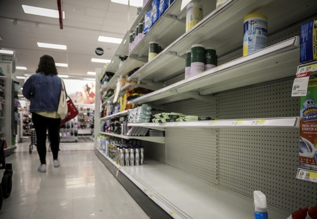 FILE - In this March 3, 2020 file photo, empty shelves for disinfectant wipes wait for restocking, as concerns grow around COVID-19,  in New York.  Le...