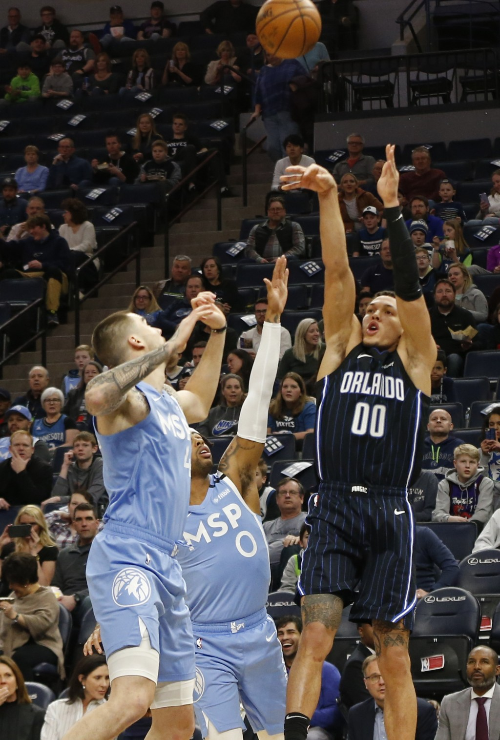 Orlando Magic's Aaron Gordon, right, shoots past Minnesota Timberwolves' Juancho Hernangomez, left, and D'Angelo Russell in the first half of an NBA b...