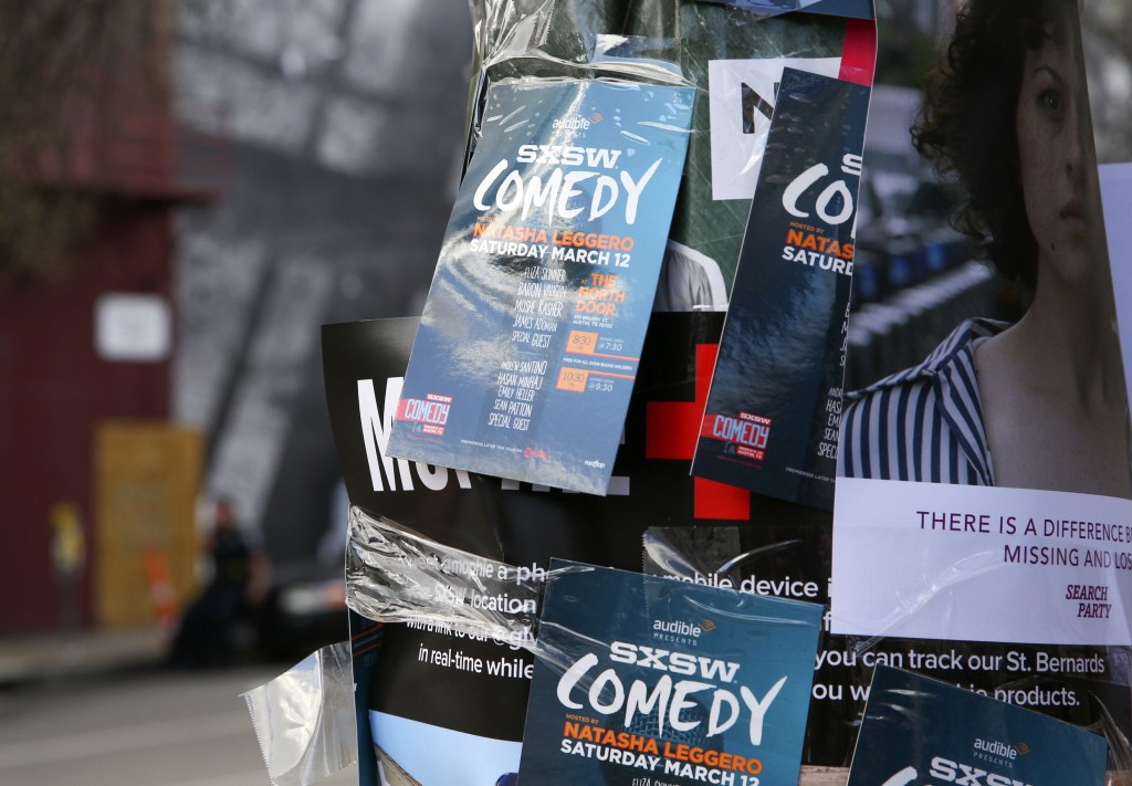 FILE - This March 12, 2016 file photo shows flyers advertising comedy on a light pole on Sixth Street during South By Southwest in Austin, Texas. Aust...
