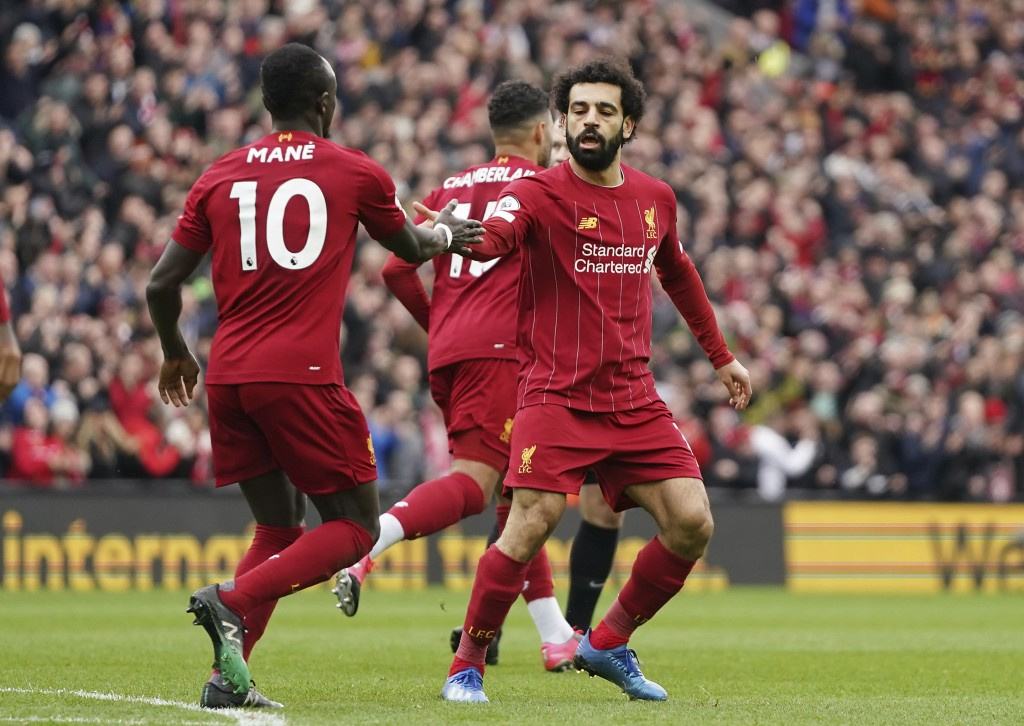 Liverpool's Mohamed Salah, right, celebrates with his teammate Sadio Mane after scoring his side's opening goal during the English Premier League socc...
