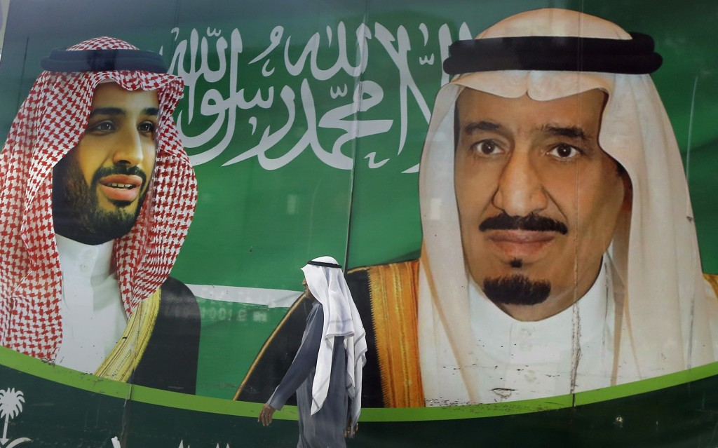 A man walks past a banner showing Saudi King Salman, right, and his Crown Prince Mohammed bin Salman, outside a mall in Jiddah, Saudi Arabia, Saturday...