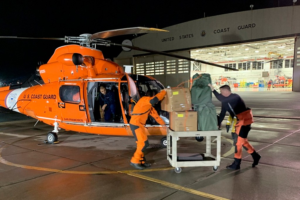 In this Friday, March 6, 2020, image provided by the U.S. Coast Guard, Air Station crew members load personal protective equipment into a helicopter i...