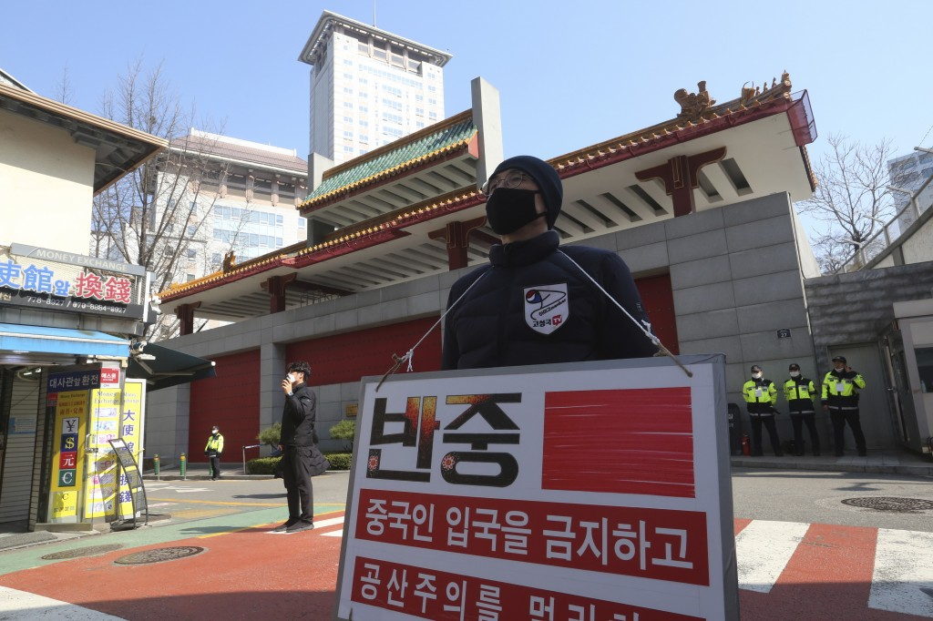A man wearing a face mask stands calling for a ban on Chinese people entering South Korea near the Chinese Embassy in Seoul, South Korea, Sunday, Marc...
