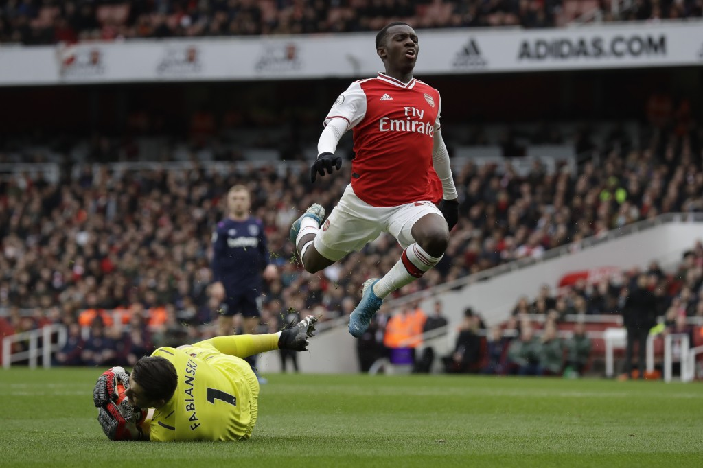 Arsenal's Edward Nketiah jumps over West Ham's goalkeeper Lukasz Fabianski during the Premier League soccer match between Arsenal and West Ham at the ...