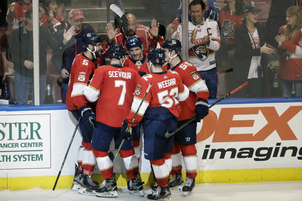 Florida Panthers left wing Mike Hoffman (68) is congratulated by teammates after he scored a goal during the third period of an NHL hockey game agains...