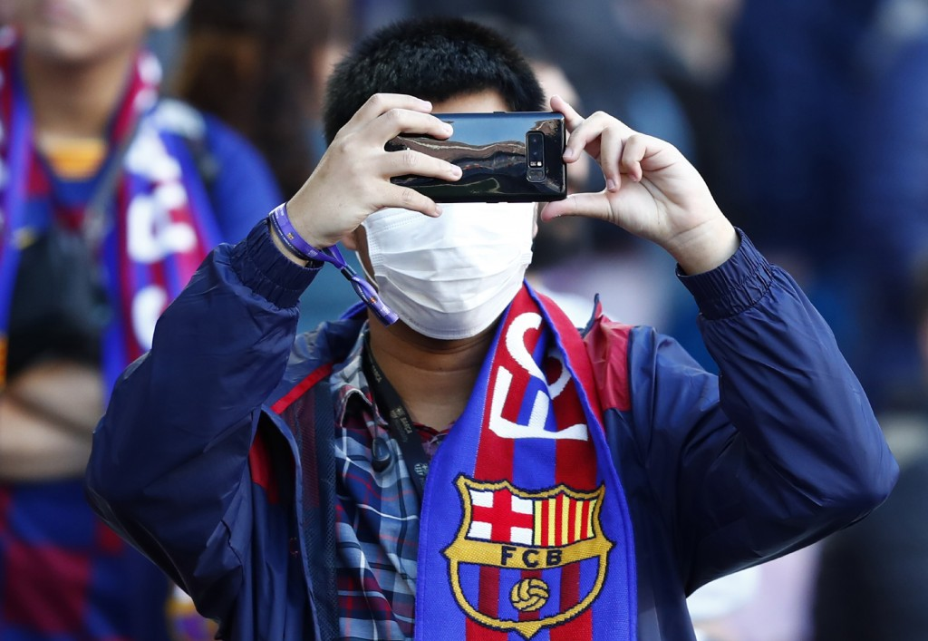 A Barcelona fan wears a face mask in an attempt to protect there self from the coronavirus uses his mobile prior a Spanish La Liga soccer match betwee...
