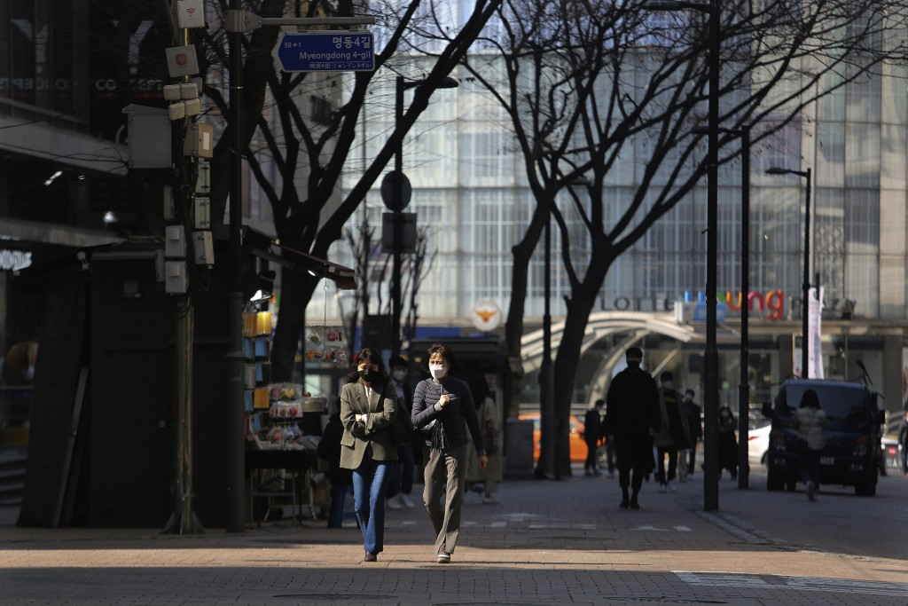 Women wearing face masks walk down a shopping street in Seoul, South Korea, Sunday, March 8, 2020. The number of infections of the COVID-19 disease sp...