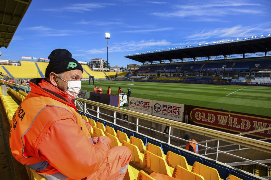 A man wears a mask as he sits in the stands ahead of a Serie A soccer match between Parma and Spal was scheduled to be played, in Parma, northern Ital...