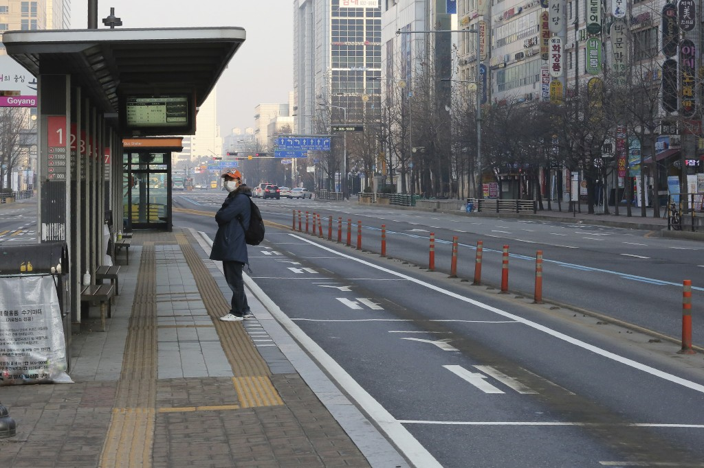 A man wearing a face mask waits for the bus at a stop in Goyang, South Korea, Sunday, March 8, 2020. The number of infections of the COVID-19 disease ...