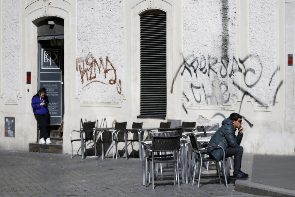 A man sits at a table as others are empty at a cafe in Largo Argentina square amid growing concern about the spread of a new coronavirus in Rome Satur...