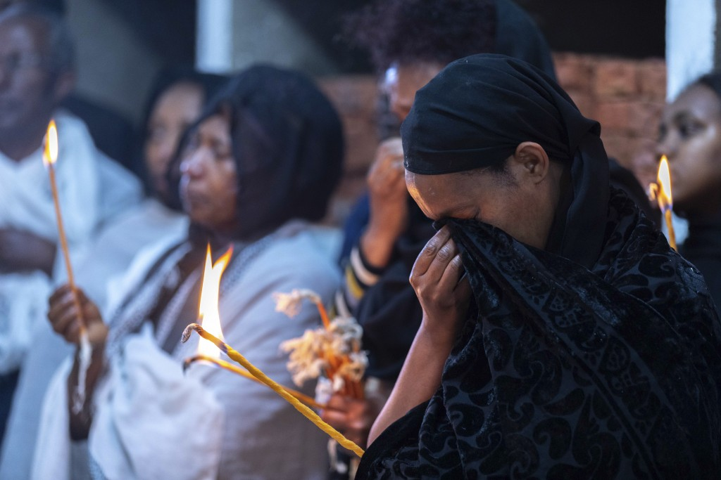 Ethiopian relatives of some of the crash victims light candles and gather at an anniversary memorial service to remember those who died when Ethiopian...