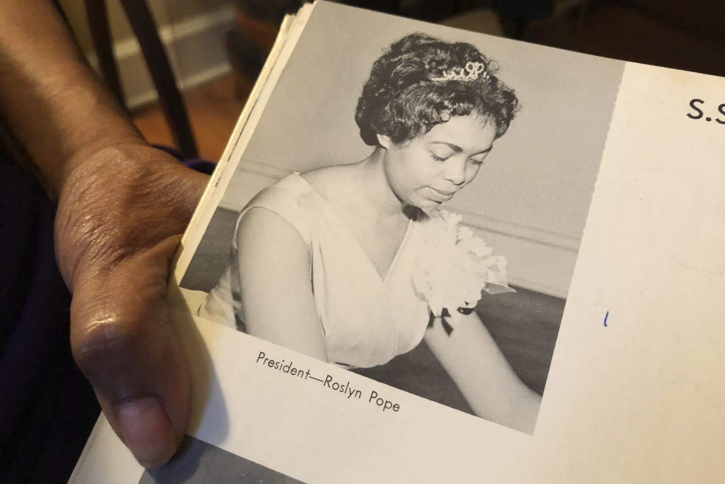 In this March 4, 2020 photo, Roslyn Pope shows her Spelman College yearbook at her home in Atlanta. As a 21-year-old Spelman senior in March 1960, Pop...