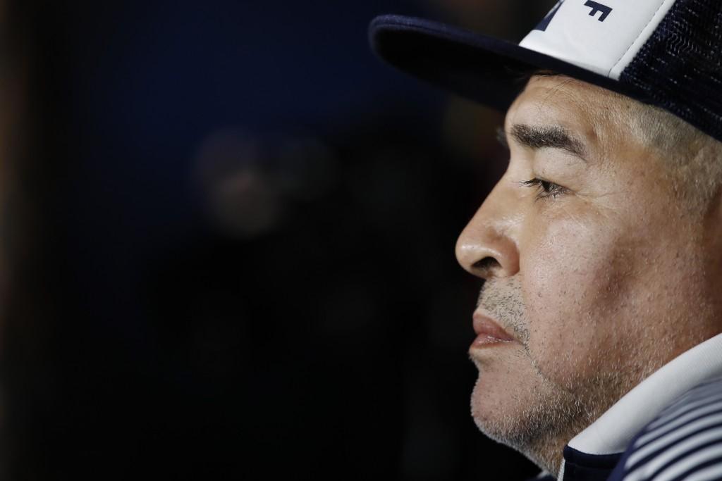 Gimnasia y Esgrima's coach Diego Maradona sits at the bench prior to an Argentina's soccer league match against Boca Juniors at La Bombonera stadium i...