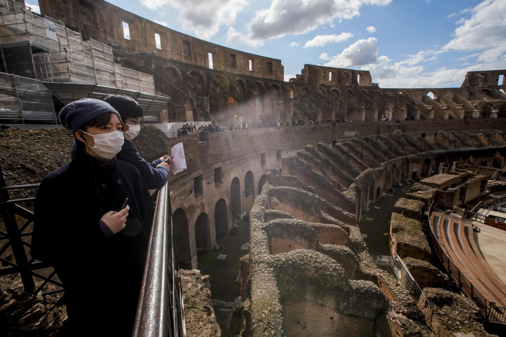 Tourists visit the Colosseum, in Rome, Saturday, March 7, 2020. With the coronavirus emergency deepening in Europe, Italy, a focal point in the contag...