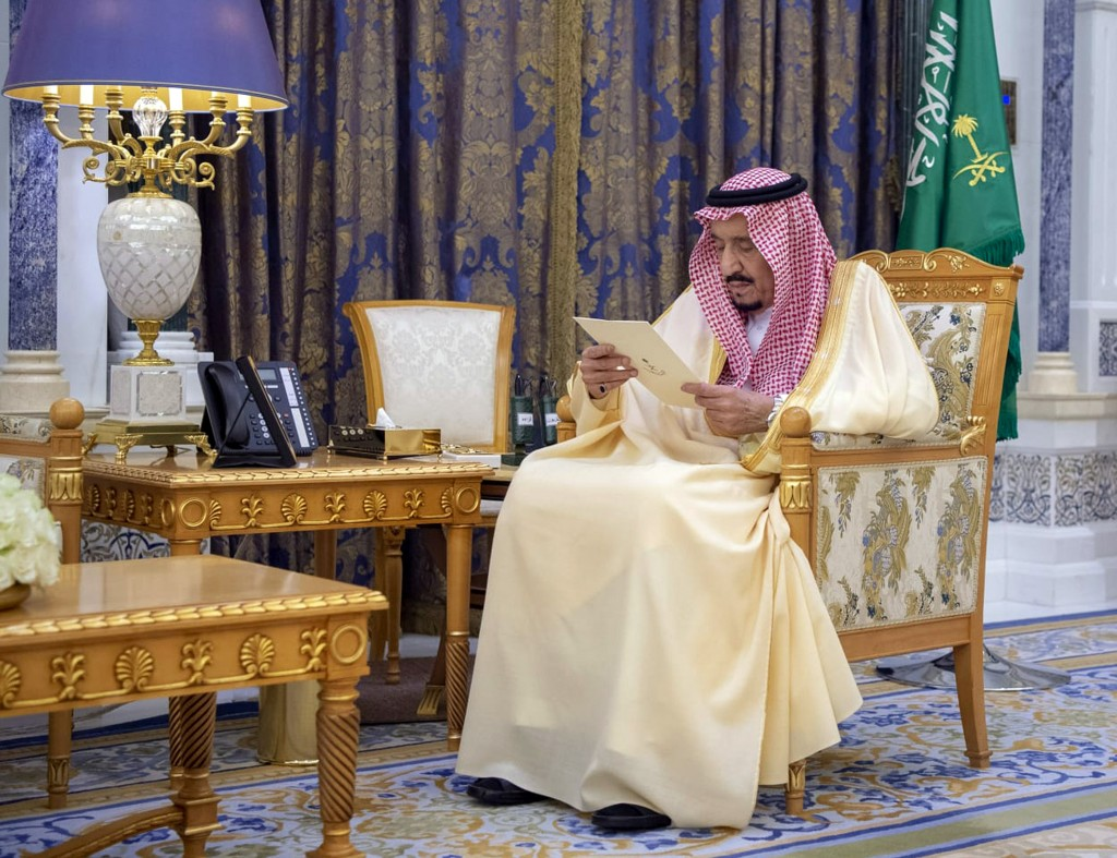 Saudi King Salman reads a document as he receives two newly appointed Saudi ambassadors at his palace in Riyadh, Saudi Arabia, Sunday, March 8, 2020. ...