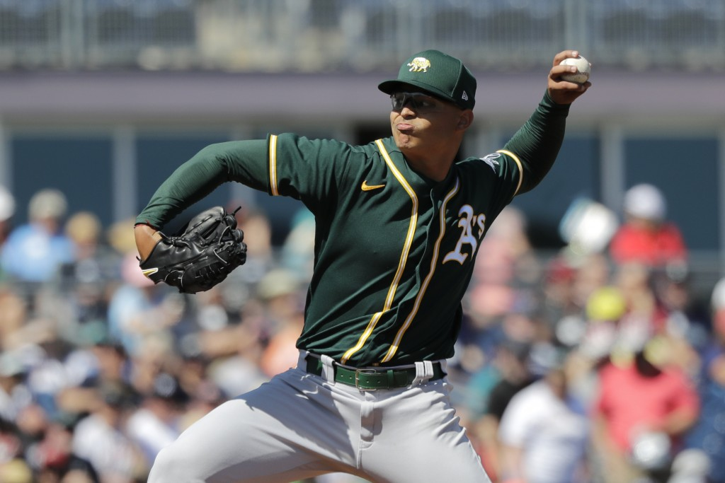 Oakland Athletics starting pitcher Jesus Luzardo throws against the Seattle Mariners in the first inning during a spring training baseball game Saturd...