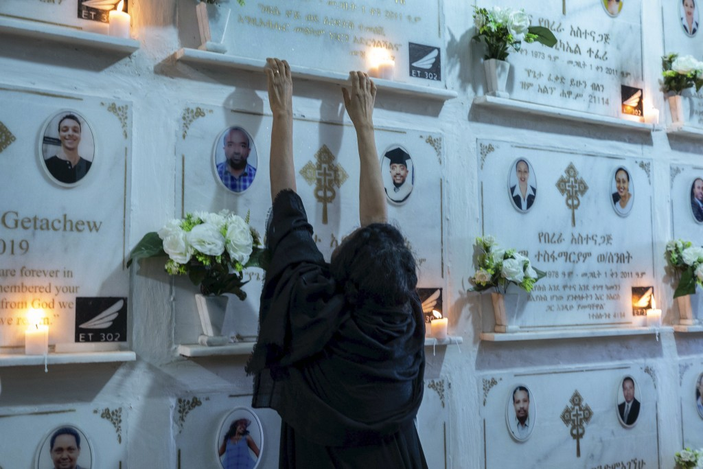 A relative reaches out as candles are lit on a memorial wall during an anniversary memorial service to remember those who died when Ethiopian Airlines...