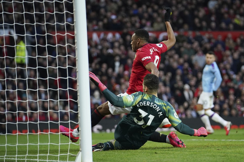 Manchester United's Anthony Martial, center top, tries to score past Manchester City's goalkeeper Ederson, bottom, during the English Premier League s...
