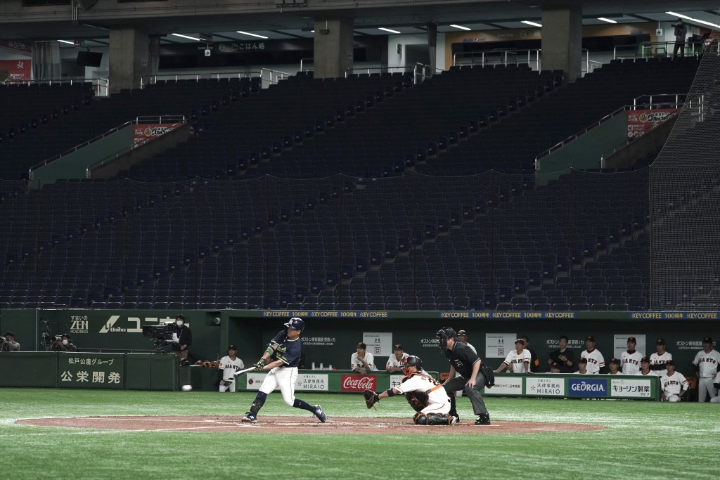 In this Feb. 29, 2020, photo, spectators' stands are empty during play in a preseason baseball game between the Yomiuri Giants and the Yakult Swallows...